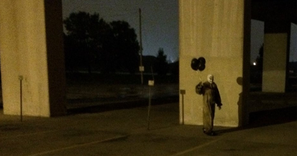 Green Bay clown carrying black balloons.