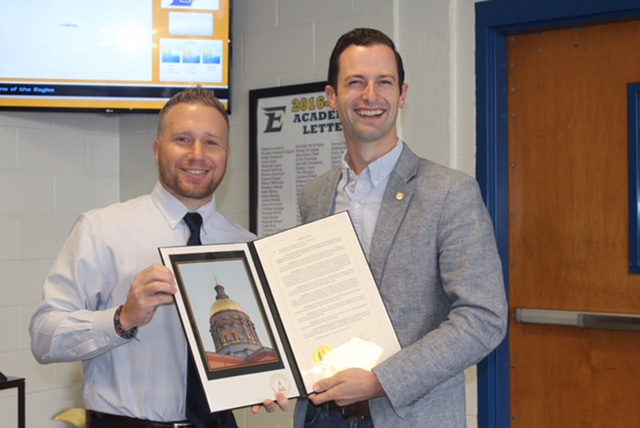 House Representative Michael Caldwell and Principal Keith Ball smile and pose for a picture with the resolution.